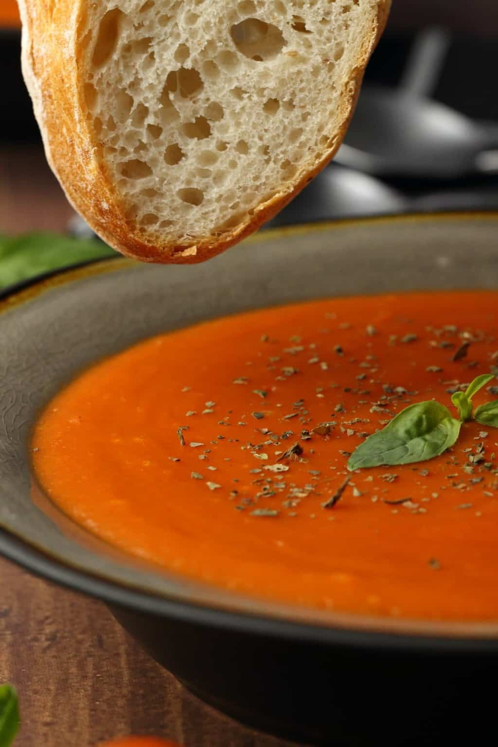 Vegan tomato soup with a slice of bread ready to dip.