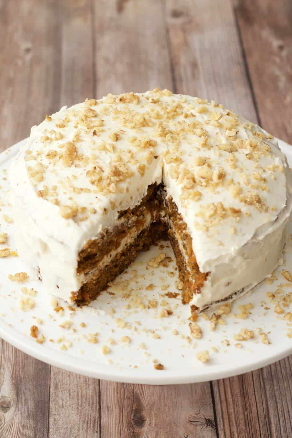 Vegan carrot cake topped with a lemon buttercream frosting and crushed walnuts on a white cake stand.