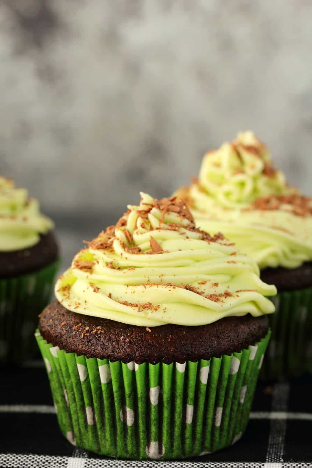 Vegan chocolate cupcakes topped with mint buttercream frosting against a dark background.