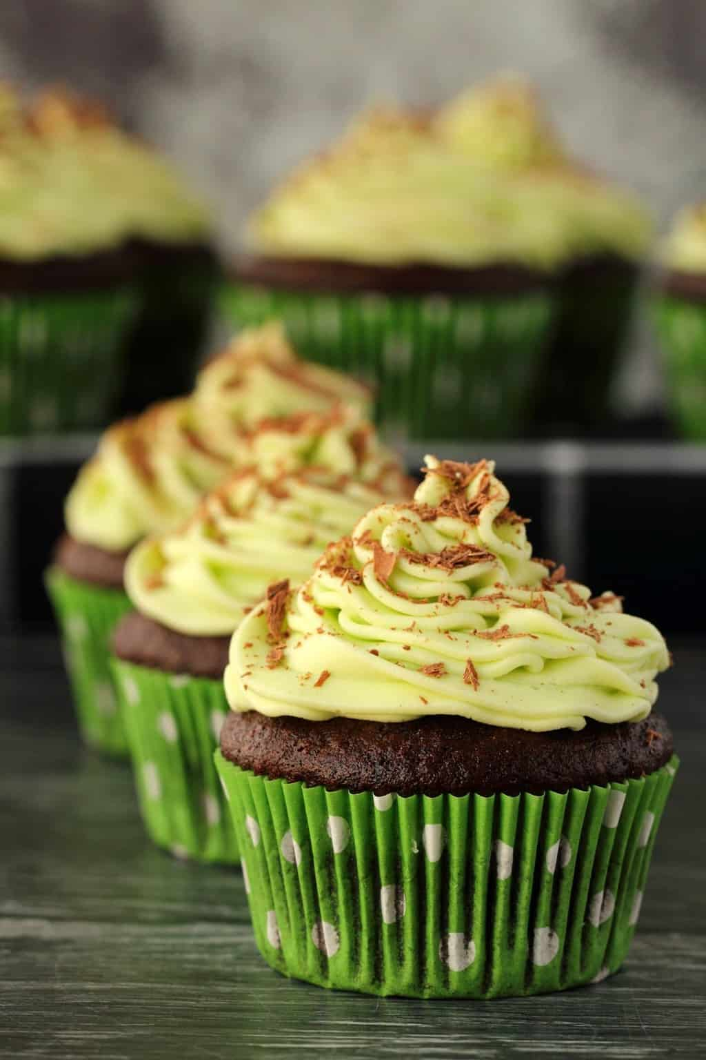 Vegan chocolate cupcakes topped with mint buttercream frosting and chocolate shavings.
