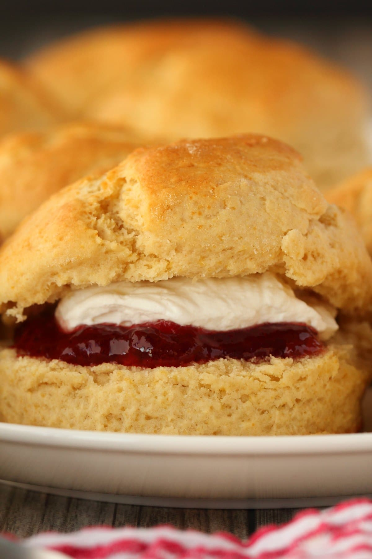 Vegan scone with jam and whipped cream in the middle, on a white plate.