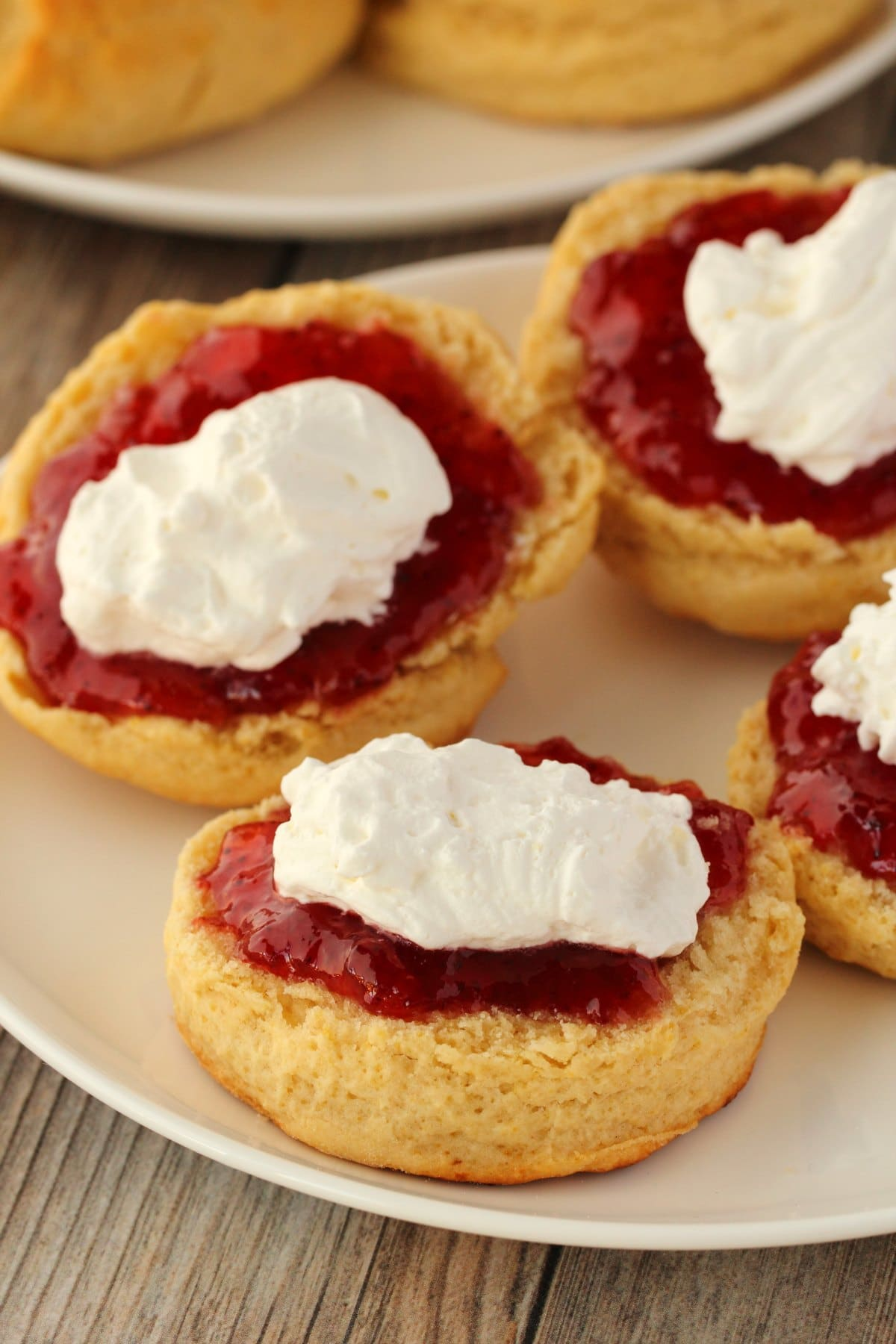 Vegan Scones topped with jam and vegan whipped cream on a white plate.