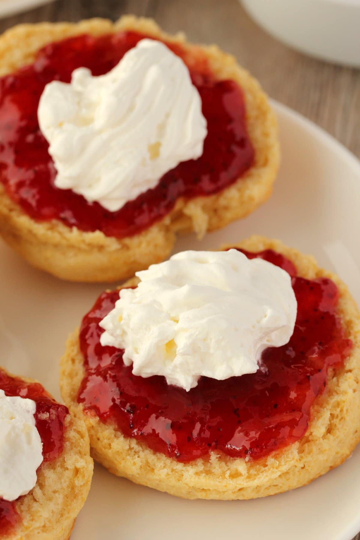 Vegan Scones topped with jam and whipped cream on a white plate.