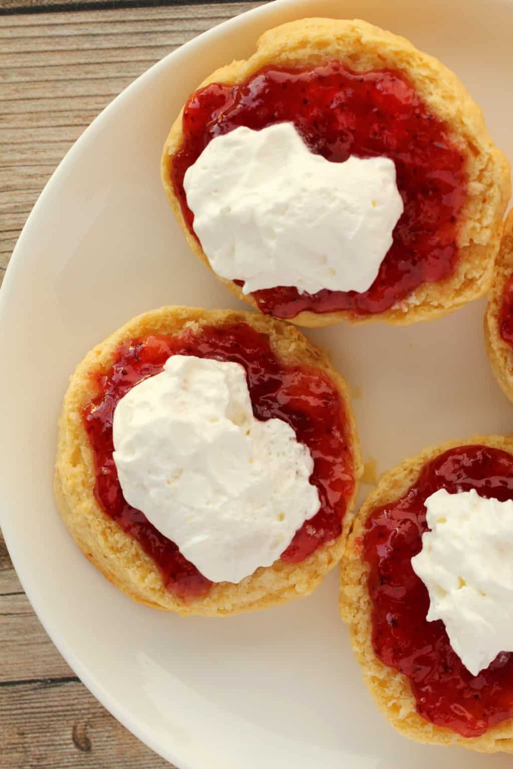 Vegan Scones topped with strawberry jam and vegan whipped cream on a white plate.