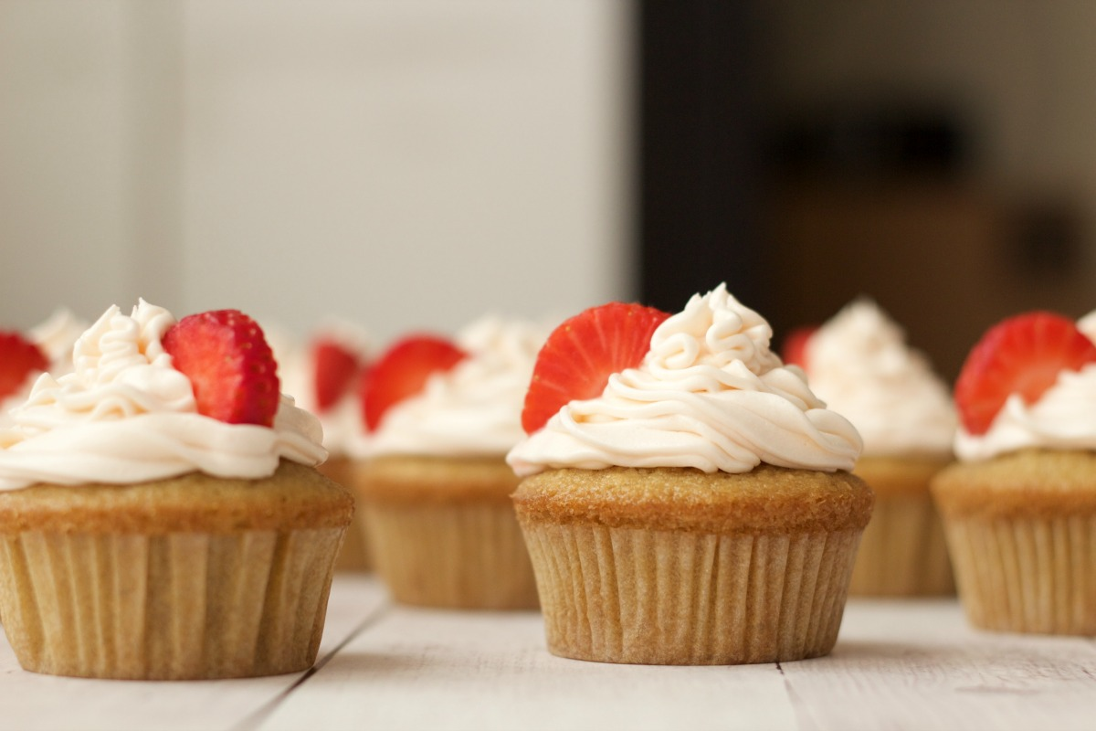 Vegan vanilla cupcakes with strawberry vanilla frosting and fresh strawberry decoration.