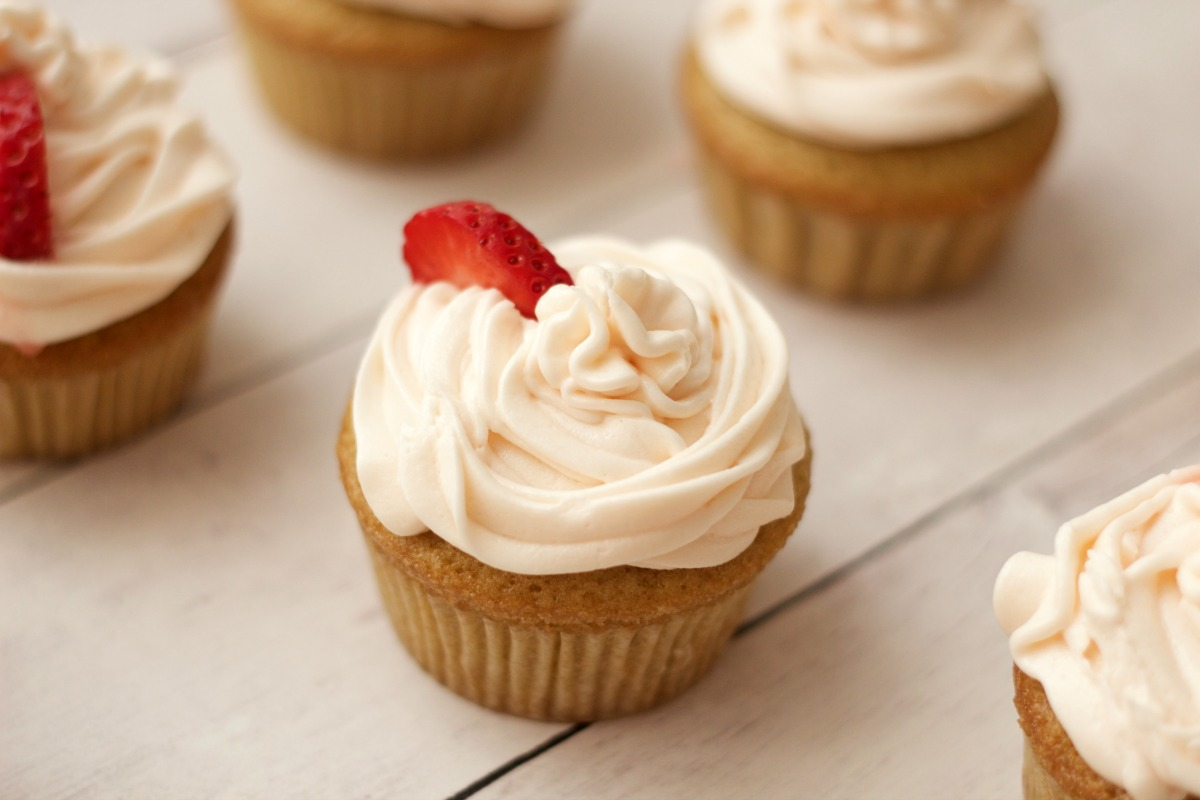 Vegan vanilla cupcakes with strawberry vanilla frosting and fresh strawberry pieces.