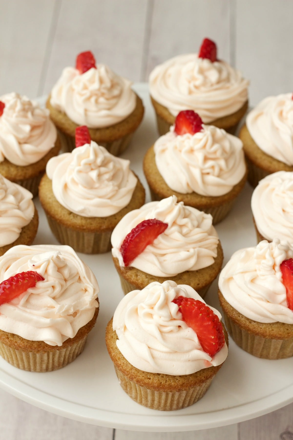 Vegan vanilla cupcakes with strawberry vanilla frosting and fresh strawberry pieces on a white cake stand.