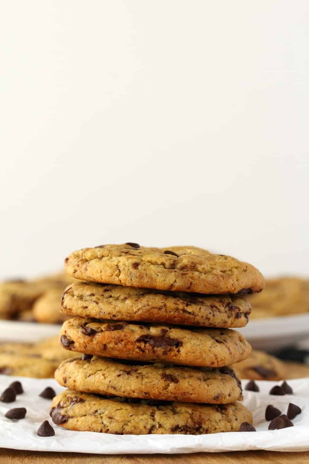 Vegan Chocolate Chip Cookies in a stack on white parchment paper.