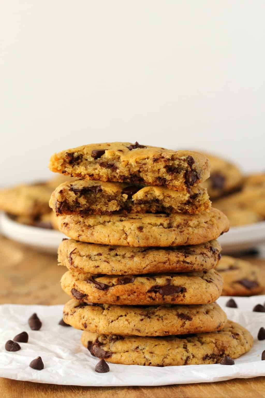 Vegan chocolate chip cookies in a stack, the top cookie broken in half to show the centers.