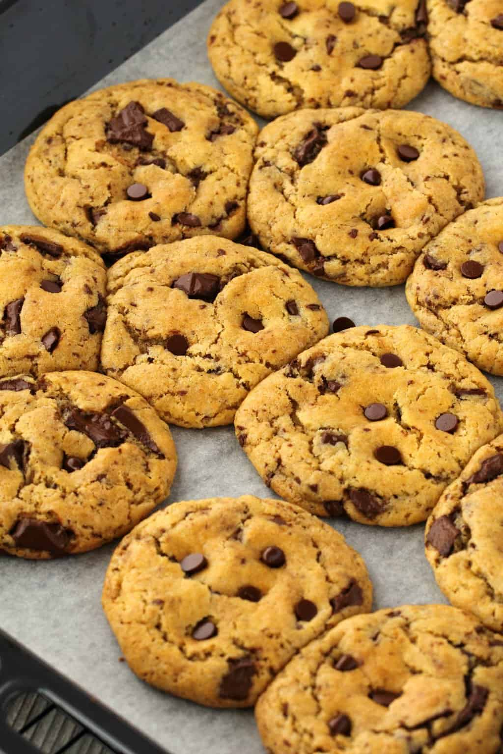 Vegan Chocolate Chip Cookies on a parchment lined baking tray, straight out of the oven.