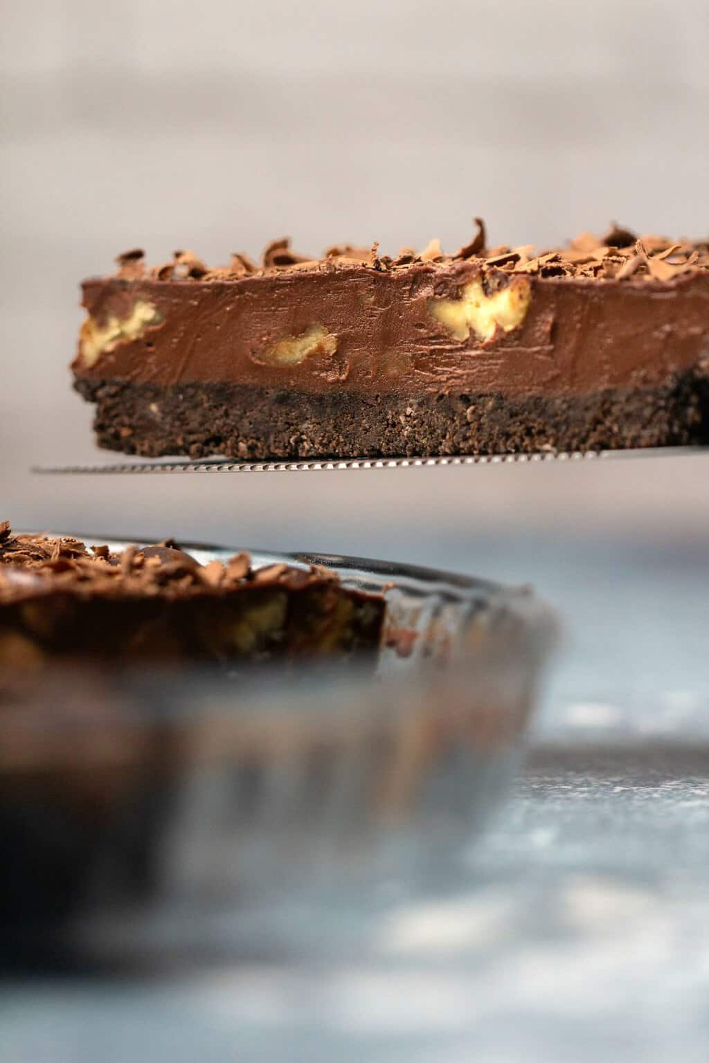 Slice of vegan chocolate tart on a cake lifter.
