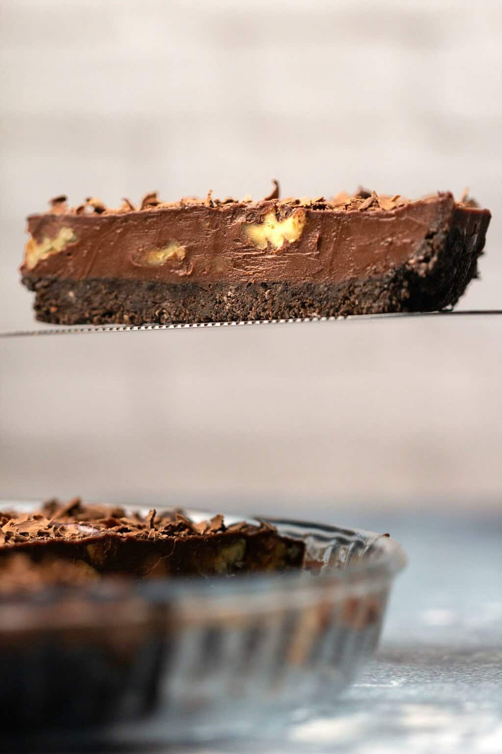 A slice of vegan chocolate tart on a cake lifter.