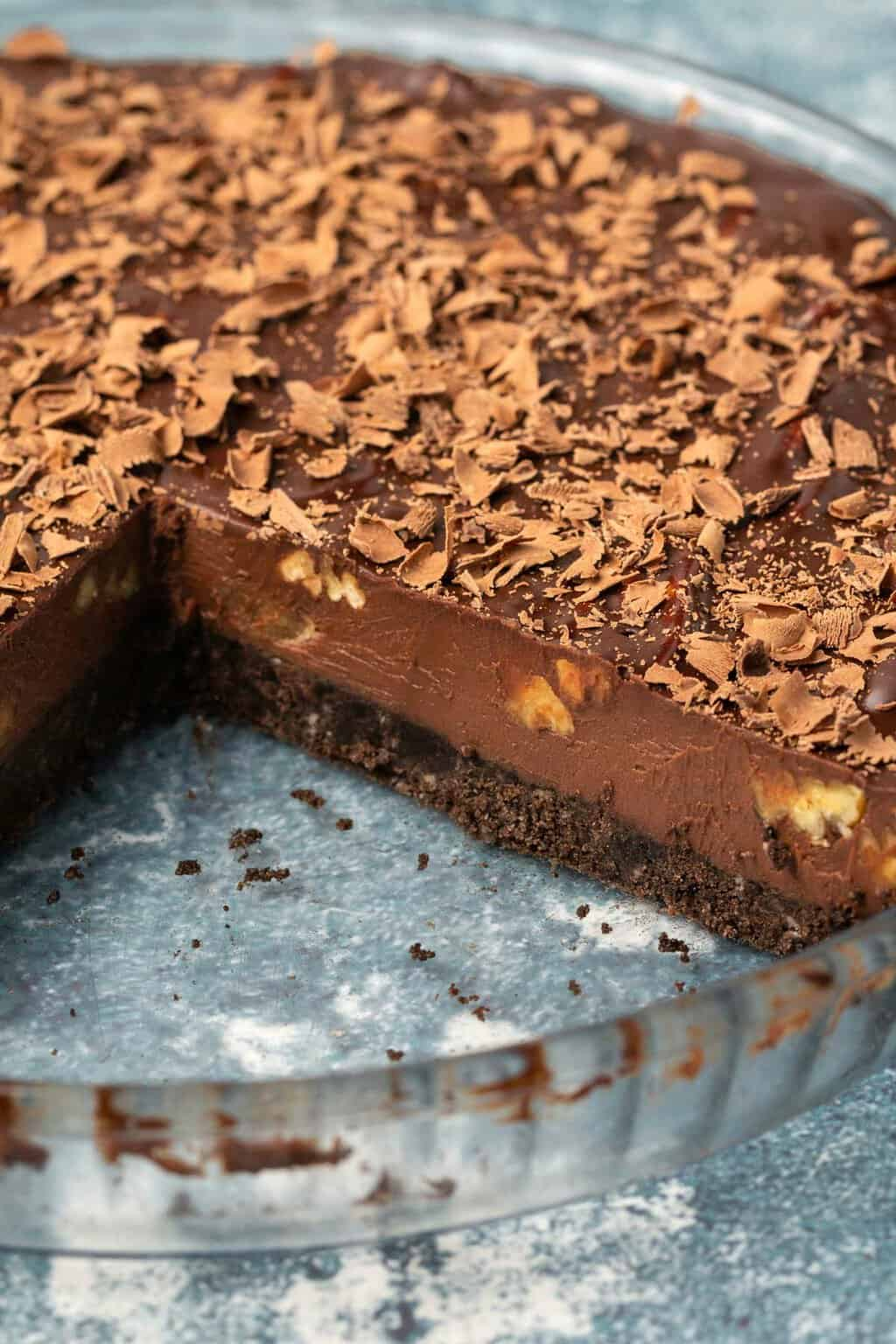 Vegan chocolate tart in a glass pie dish with one slice removed.