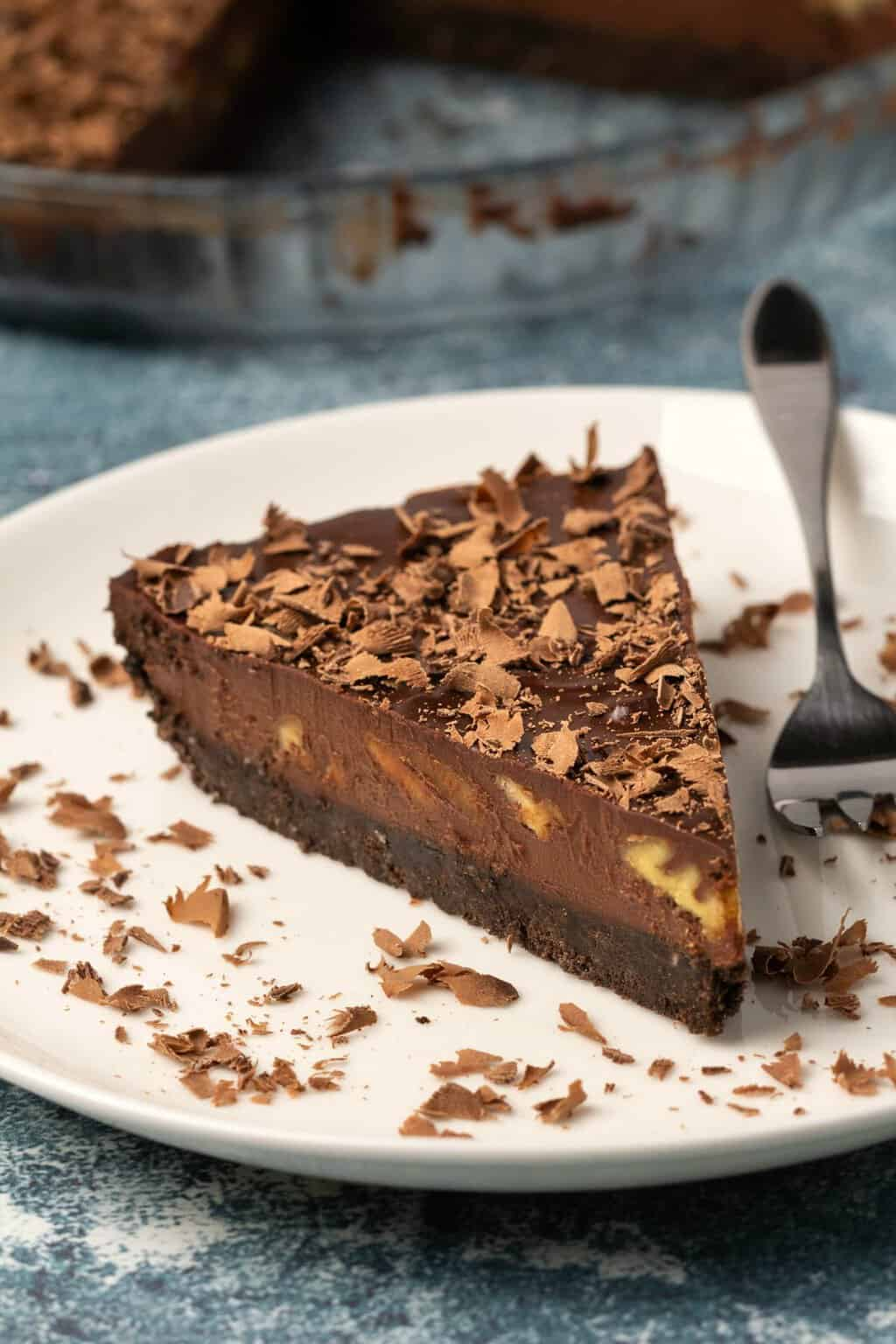 Slice of vegan chocolate tart on a white plate with a cake fork.