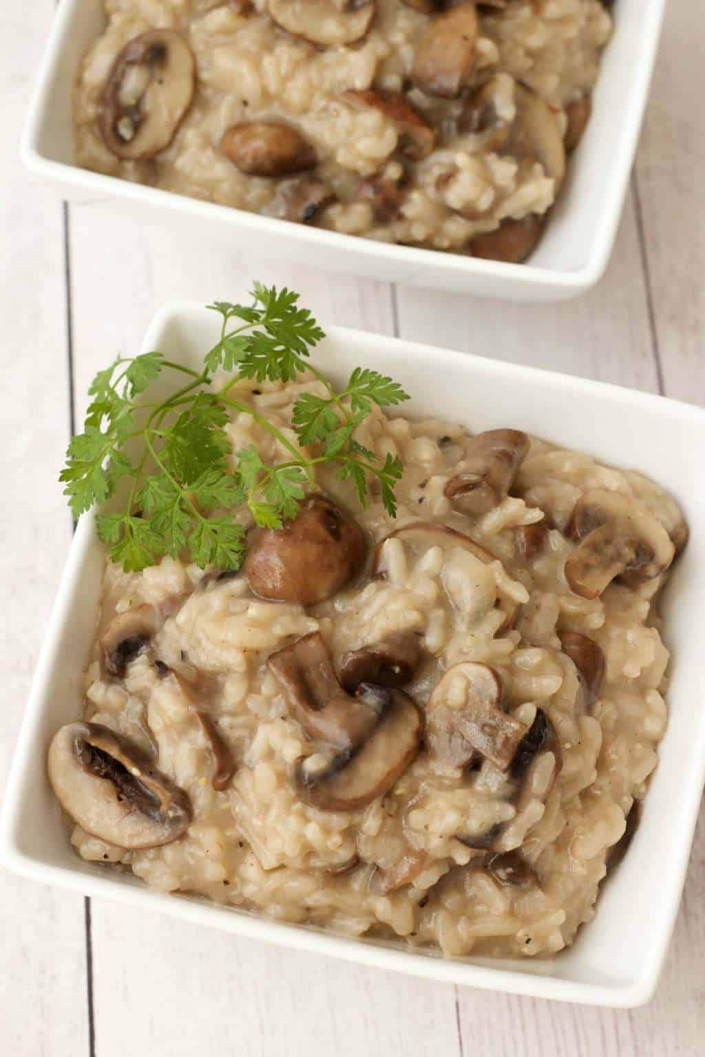 Vegan mushroom risotto topped with fresh parsley in white bowls.
