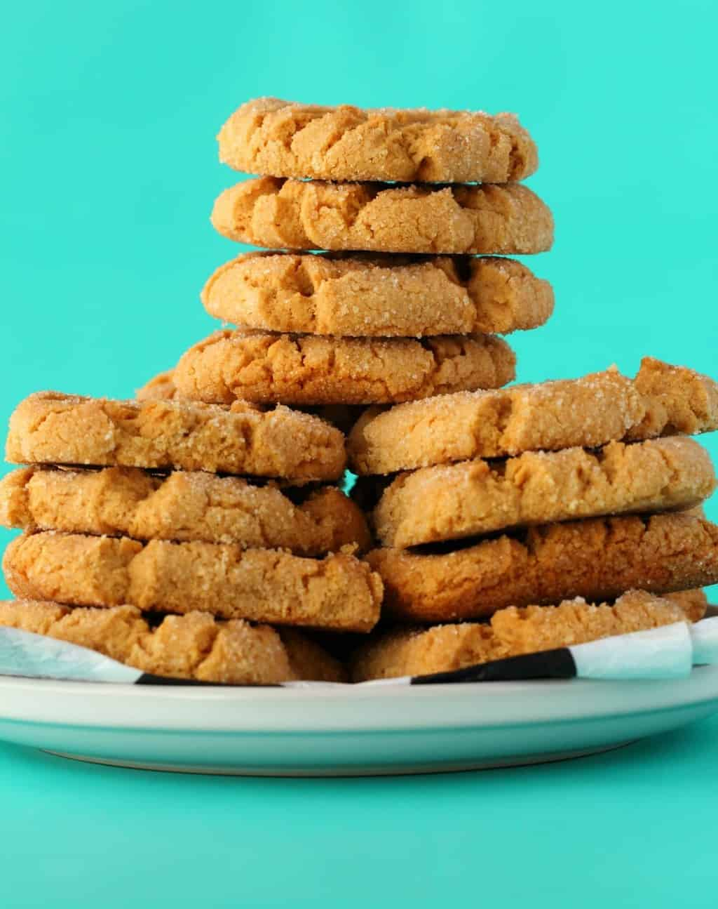 Vegan Peanut Butter Cookies stacked up on a white plate.
