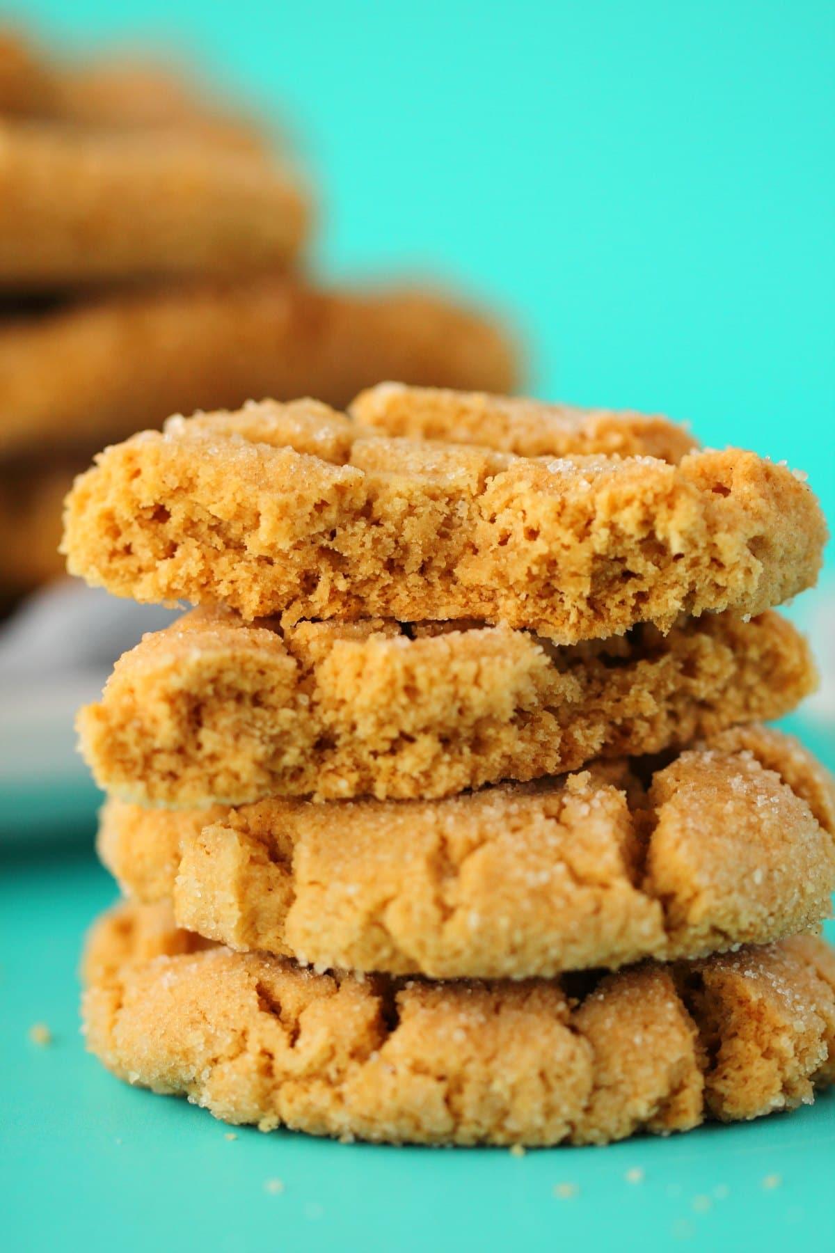 A stack of vegan peanut butter cookies with the top cookie broken in half.