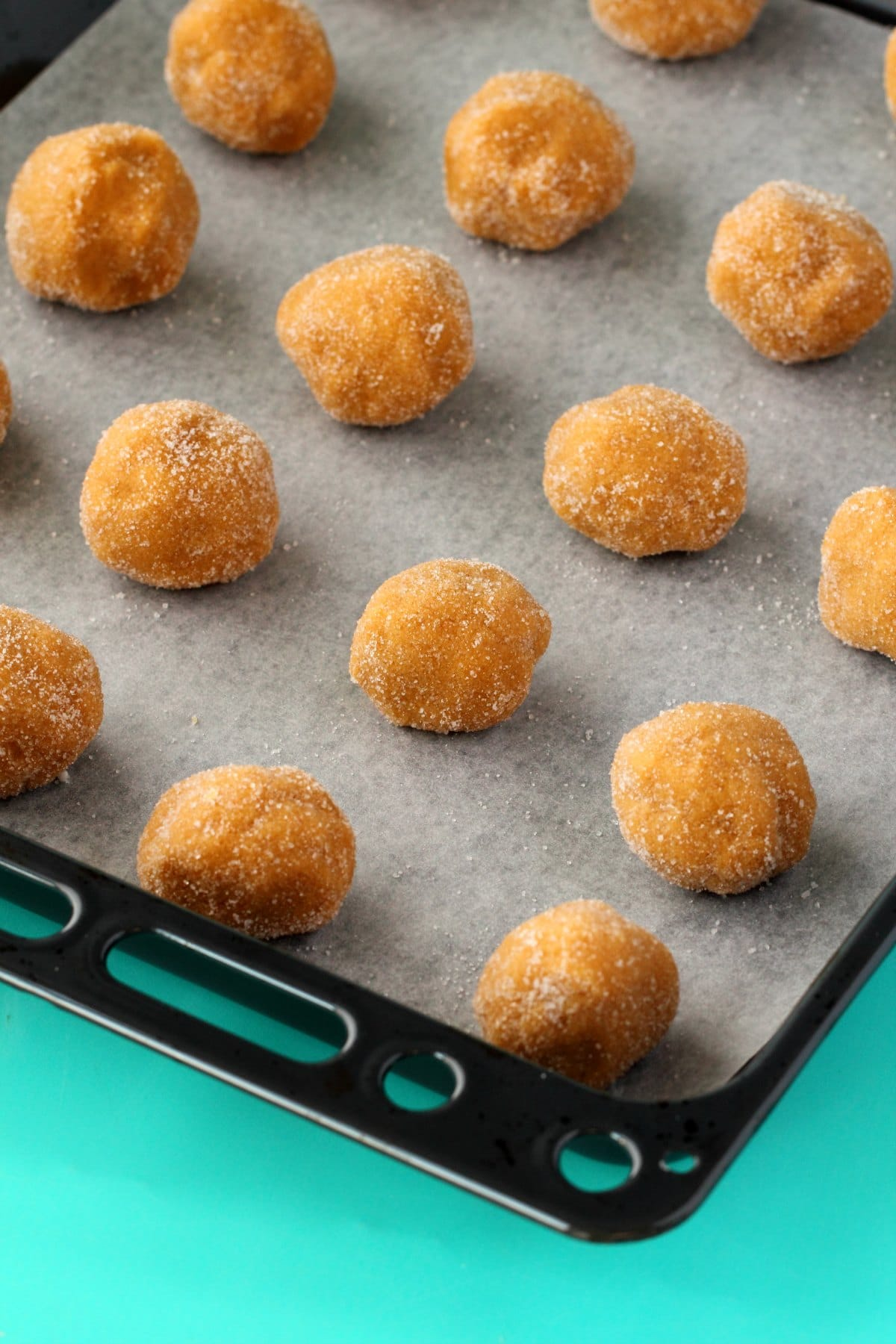 Vegan Peanut Butter Cookie dough rolled into balls on a parchment lined baking tray.