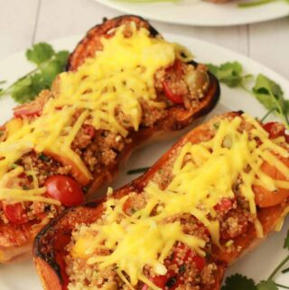 Roasted stuffed butternut squashes on a white plate.