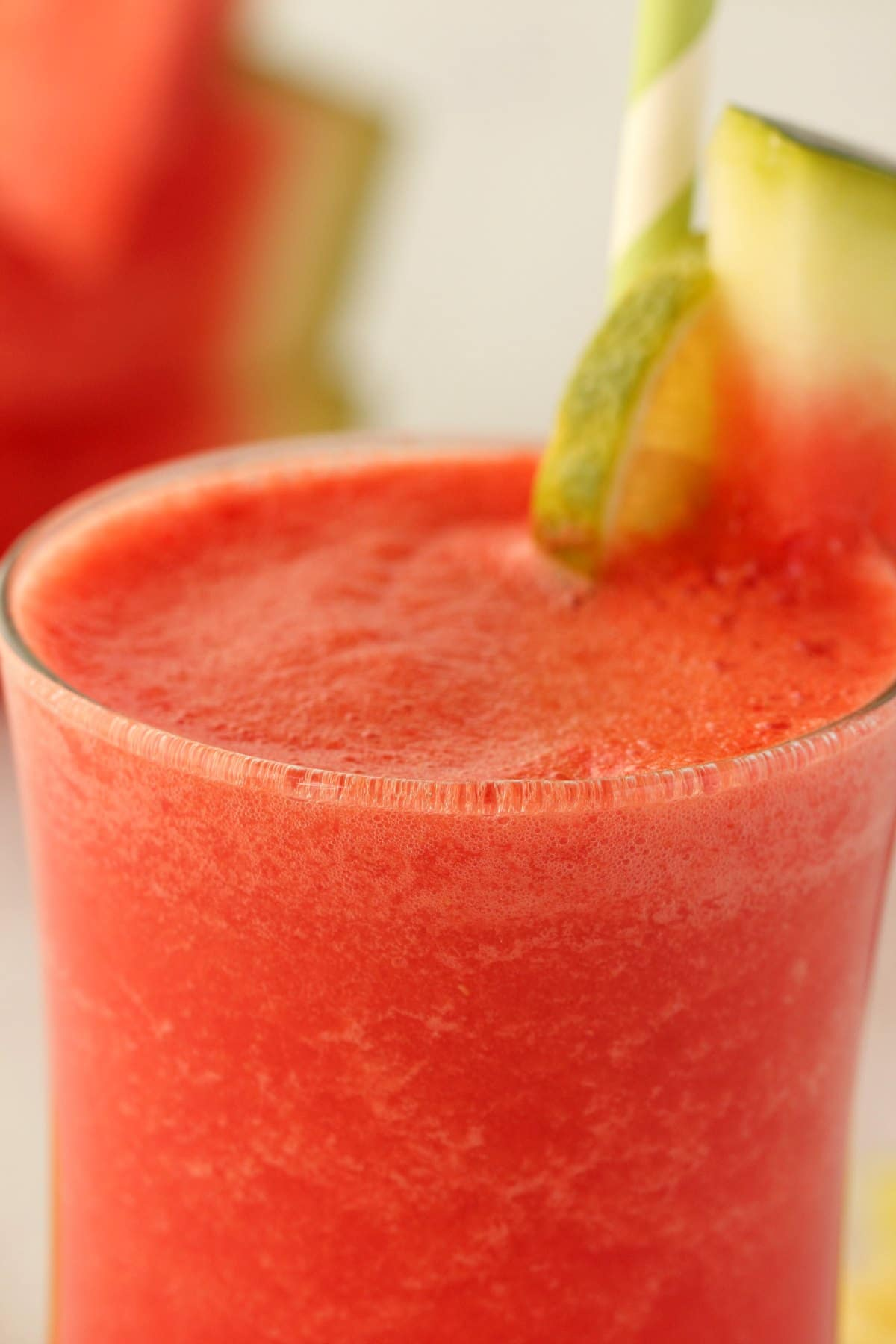 Watermelon Smoothie in a glass with a green and white straw.