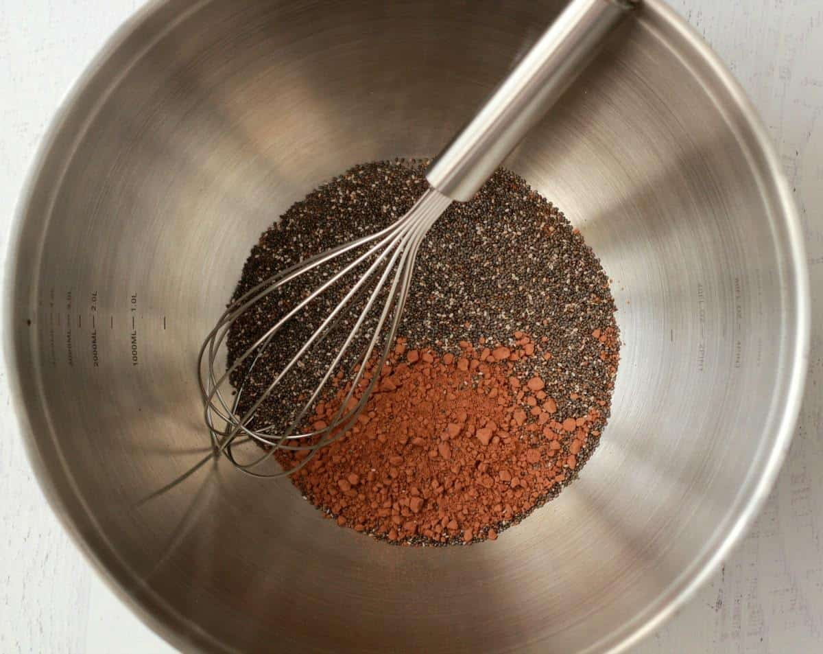 Chia seeds and cocoa powder in a mixing bowl, ready to make chocolate chia pudding.