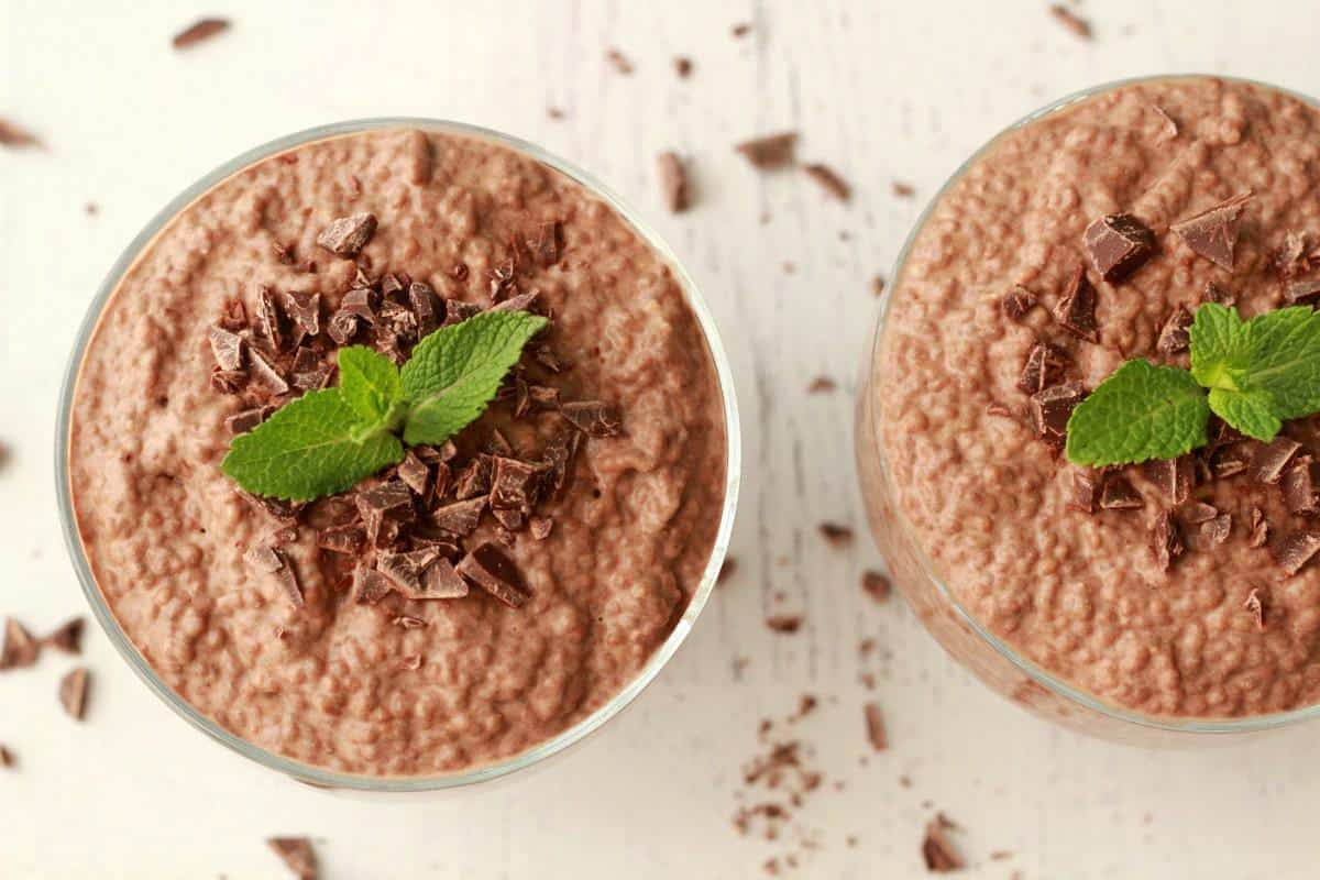 Chocolate chia pudding in glass bowls, topped with chocolate pieces and fresh mint leaves.