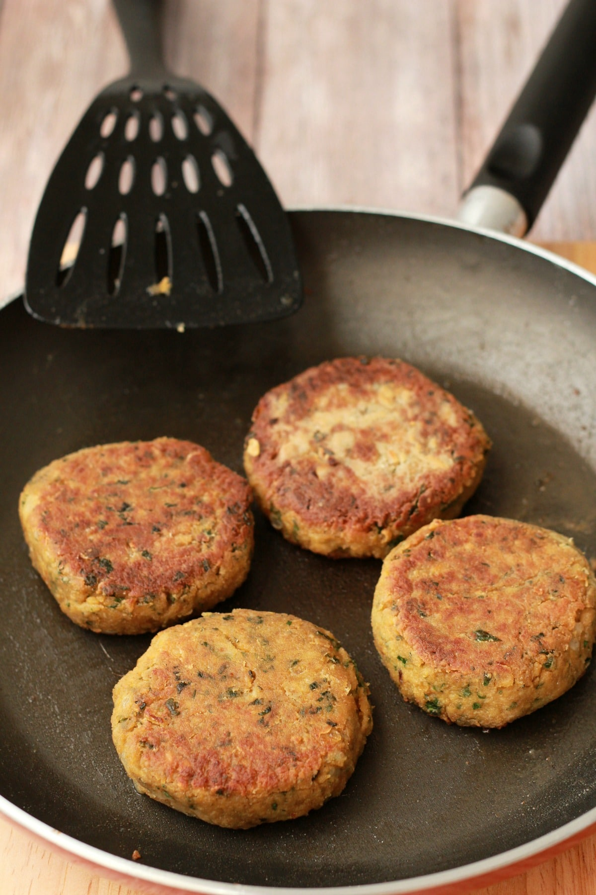 Vegan chickpea burgers nicely browned in a frying pan with a spatula.