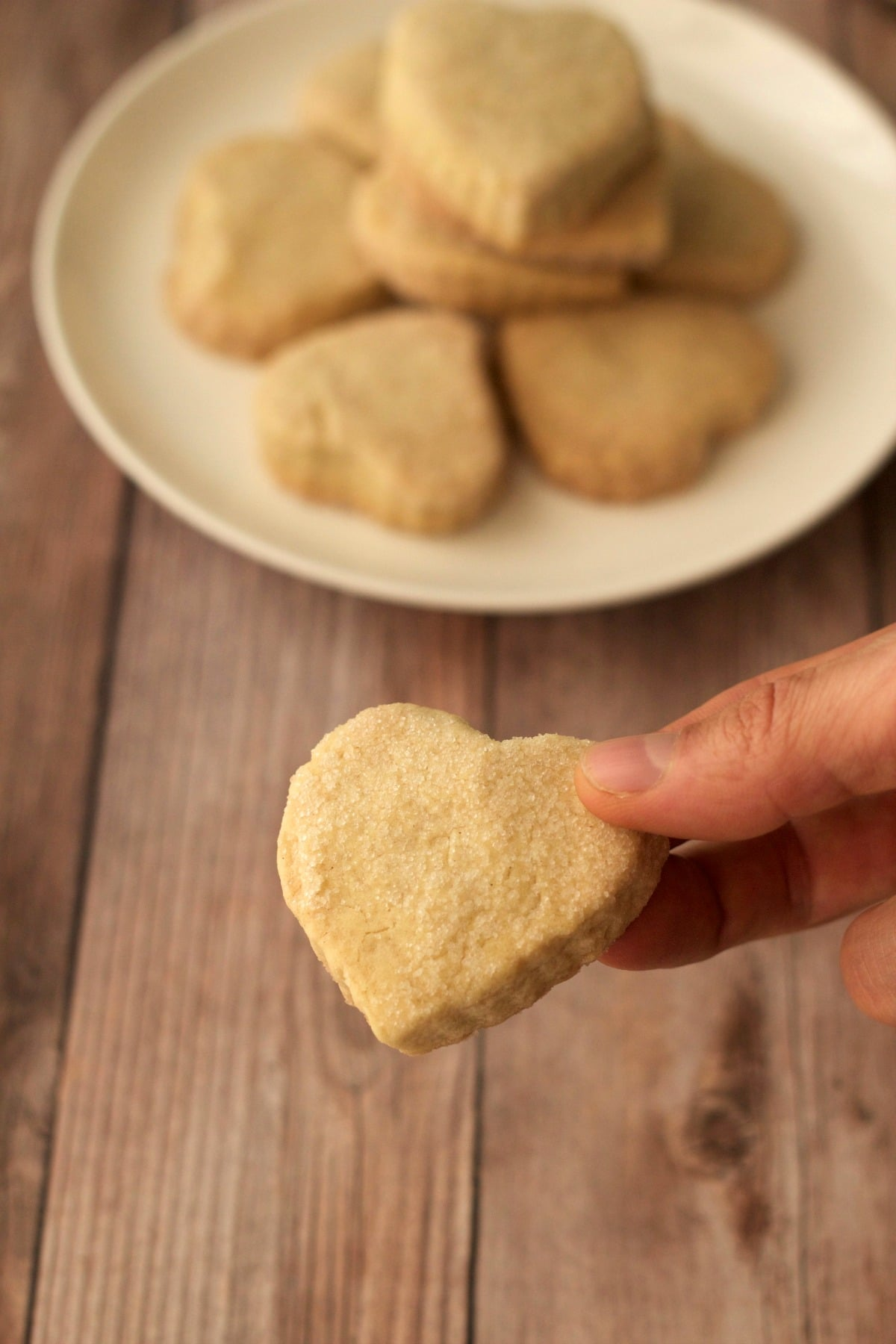 A vegan shortbread cookie with a plate of cookies in the background.