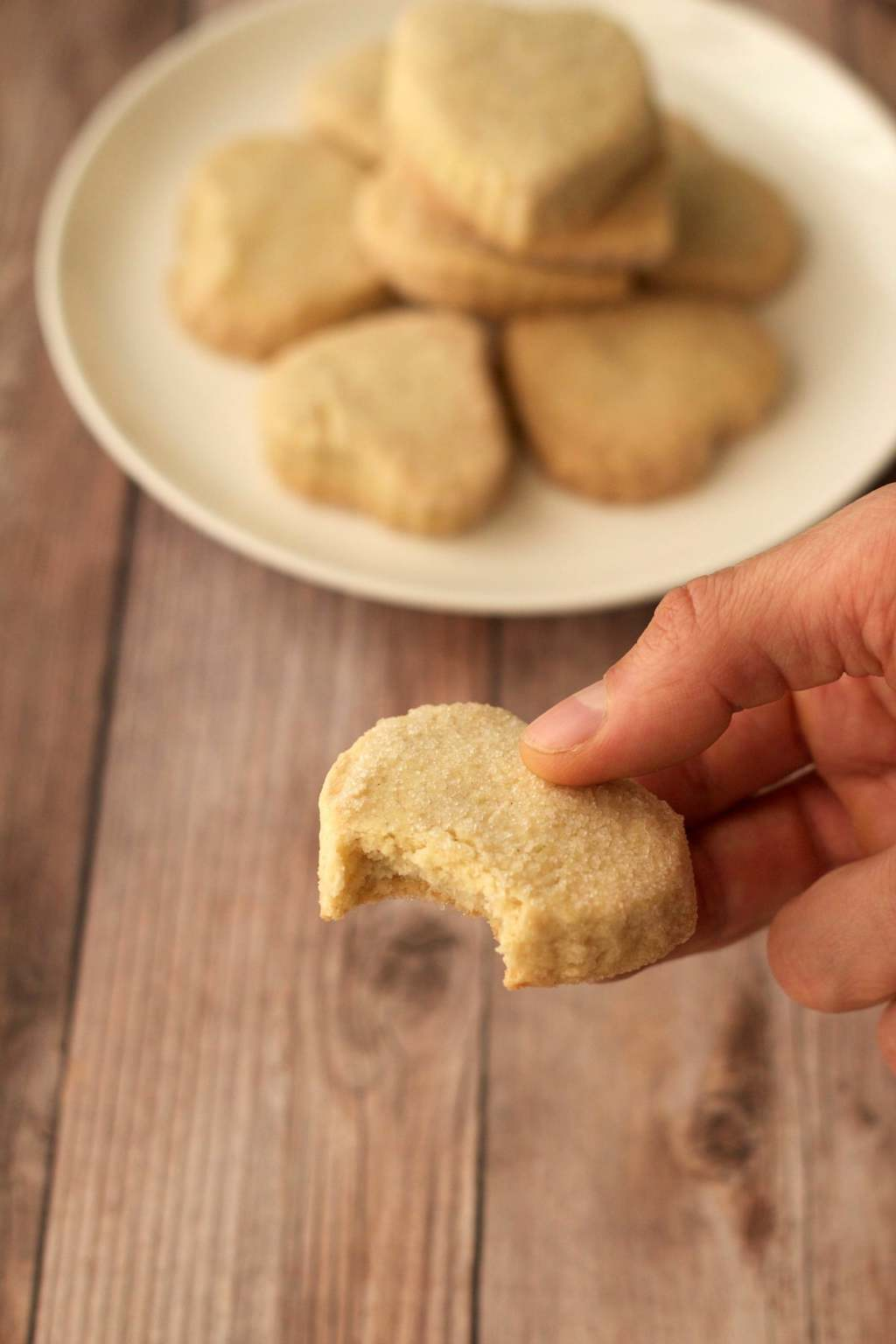A vegan shortbread cookie with a bite taken out of it.