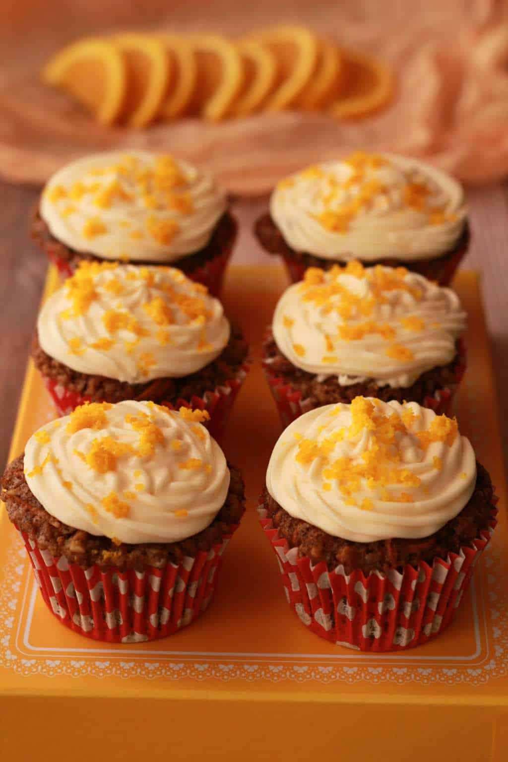 Carrot cake cupcakes on top of an orange box.