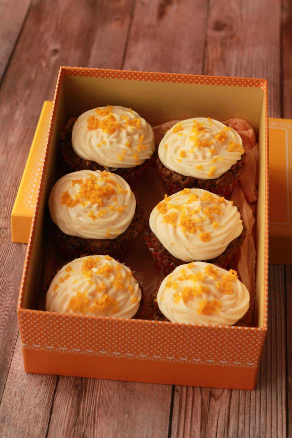 Carrot cake cupcakes topped with orange frosting and orange zest in an orange box.