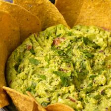 Vegan guacamole with tortilla chips in a bowl.
