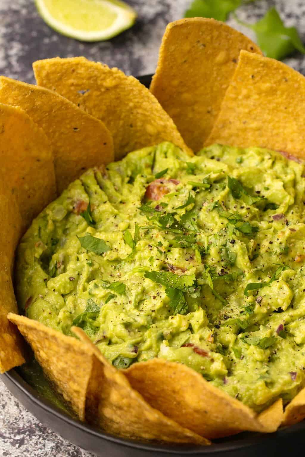 Vegan guacamole with tortilla chips in a black bowl.