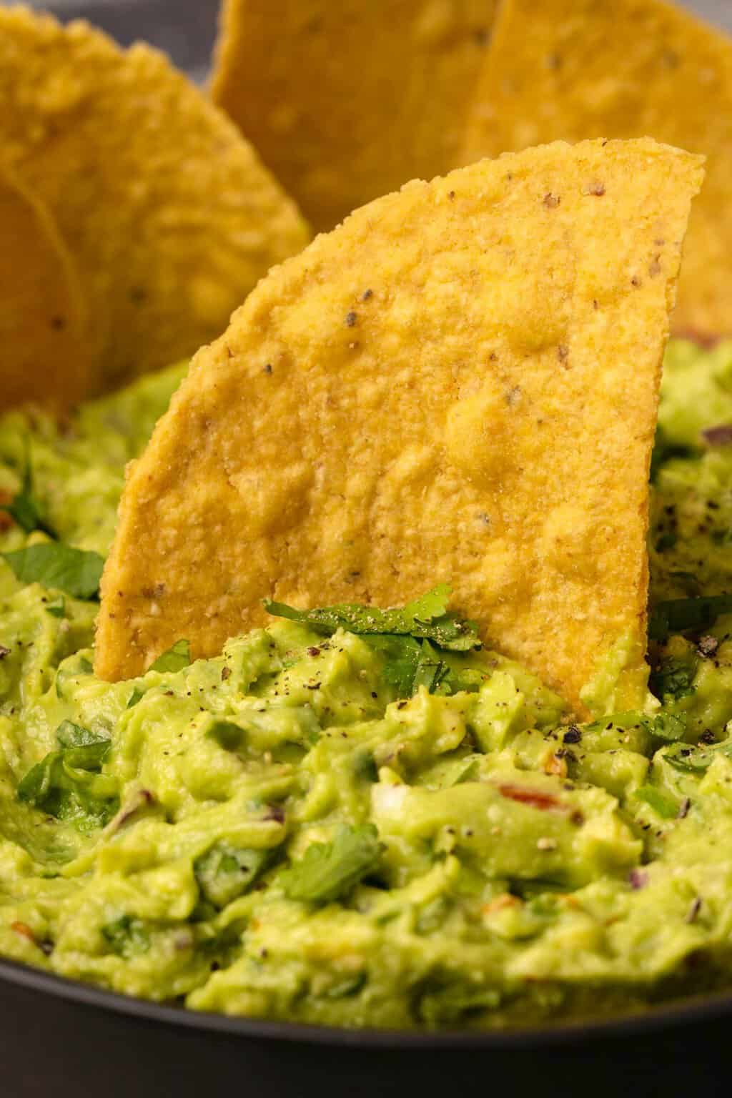 Tortilla chip dipping into a bowl of vegan guacamole.