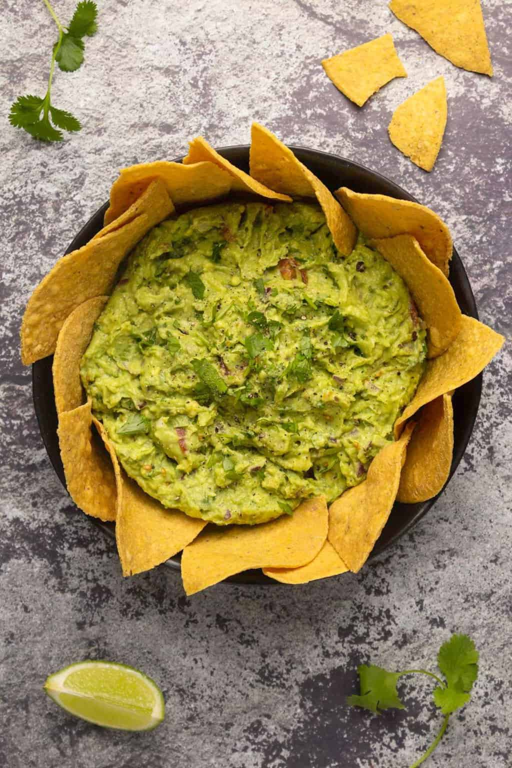 Vegan guacamole surrounded by tortilla chips in a black bowl.