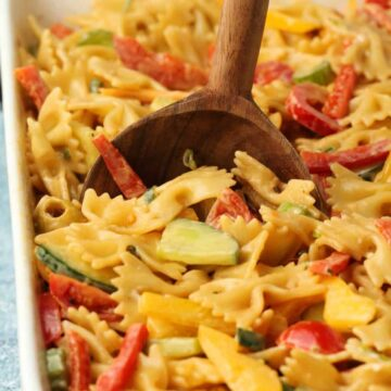 Vegan pasta salad in a white dish with a wooden serving spoon.