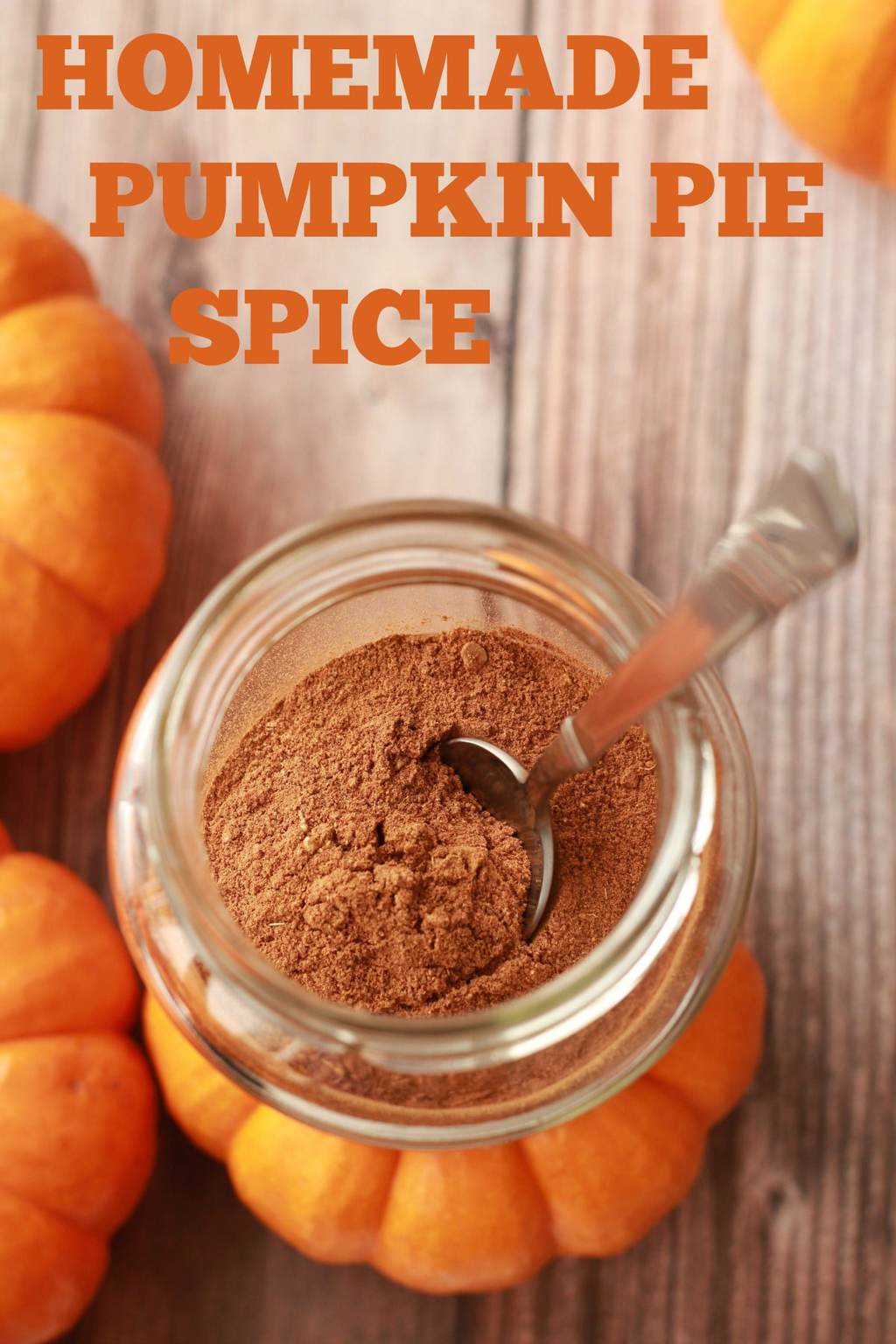 Homemade pumpkin pie spice in a glass jar with a spoon.