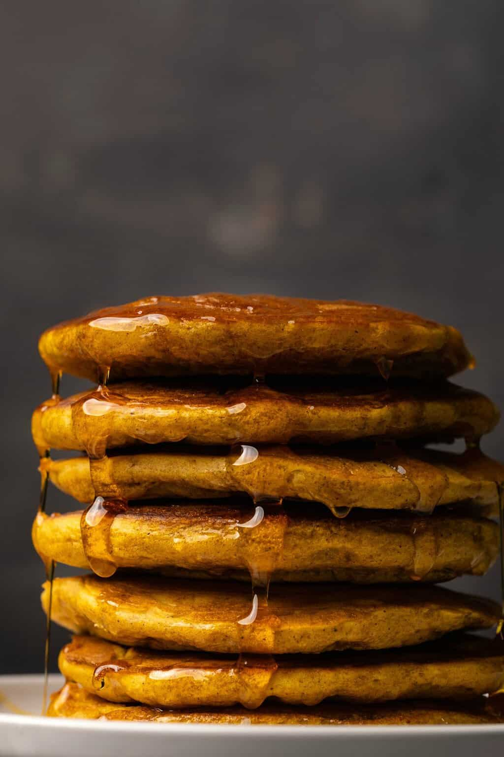 A stack of vegan pumpkin pancakes drizzled with syrup on a white plate.