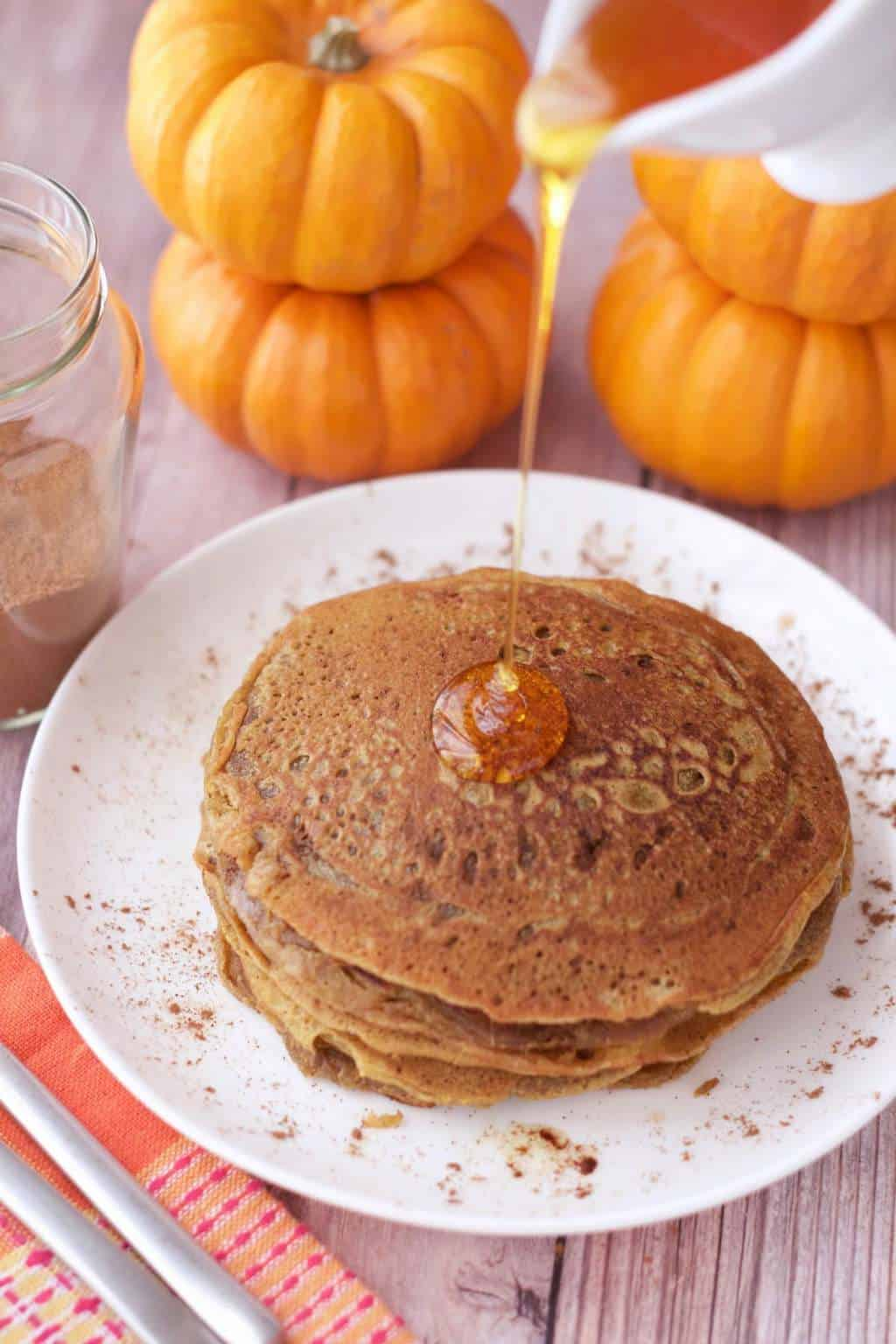 A stack of vegan pumpkin pancakes on a white plate with syrup pouring over the top.