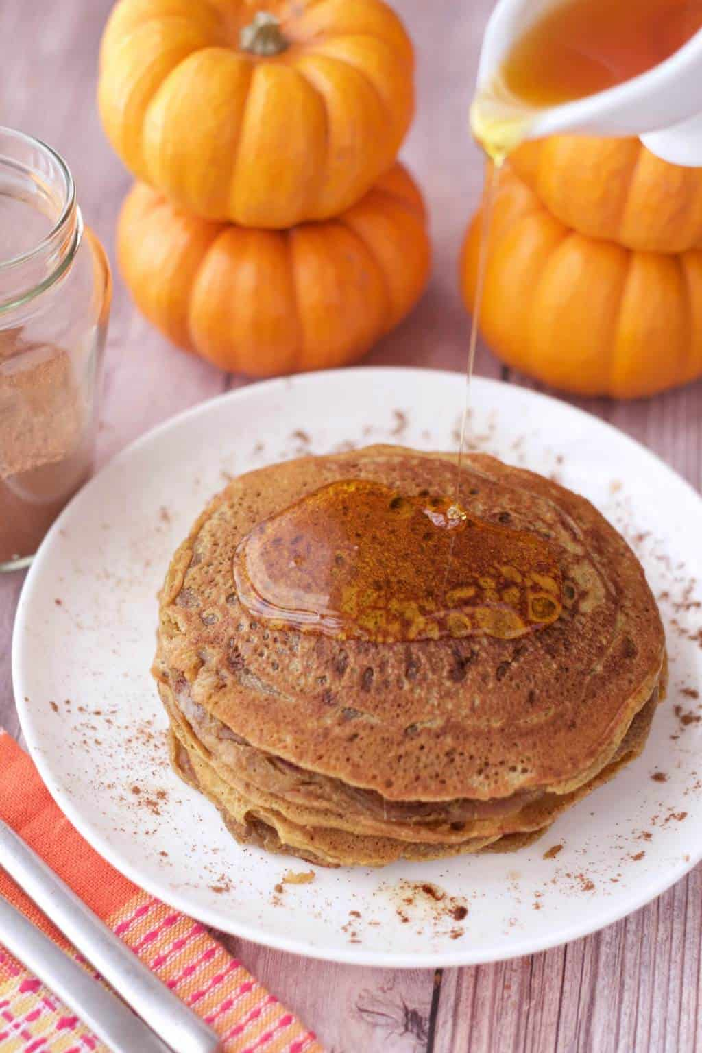 A stack of vegan pumpkin pancakes on a white plate with syrup pouring over the top of them.