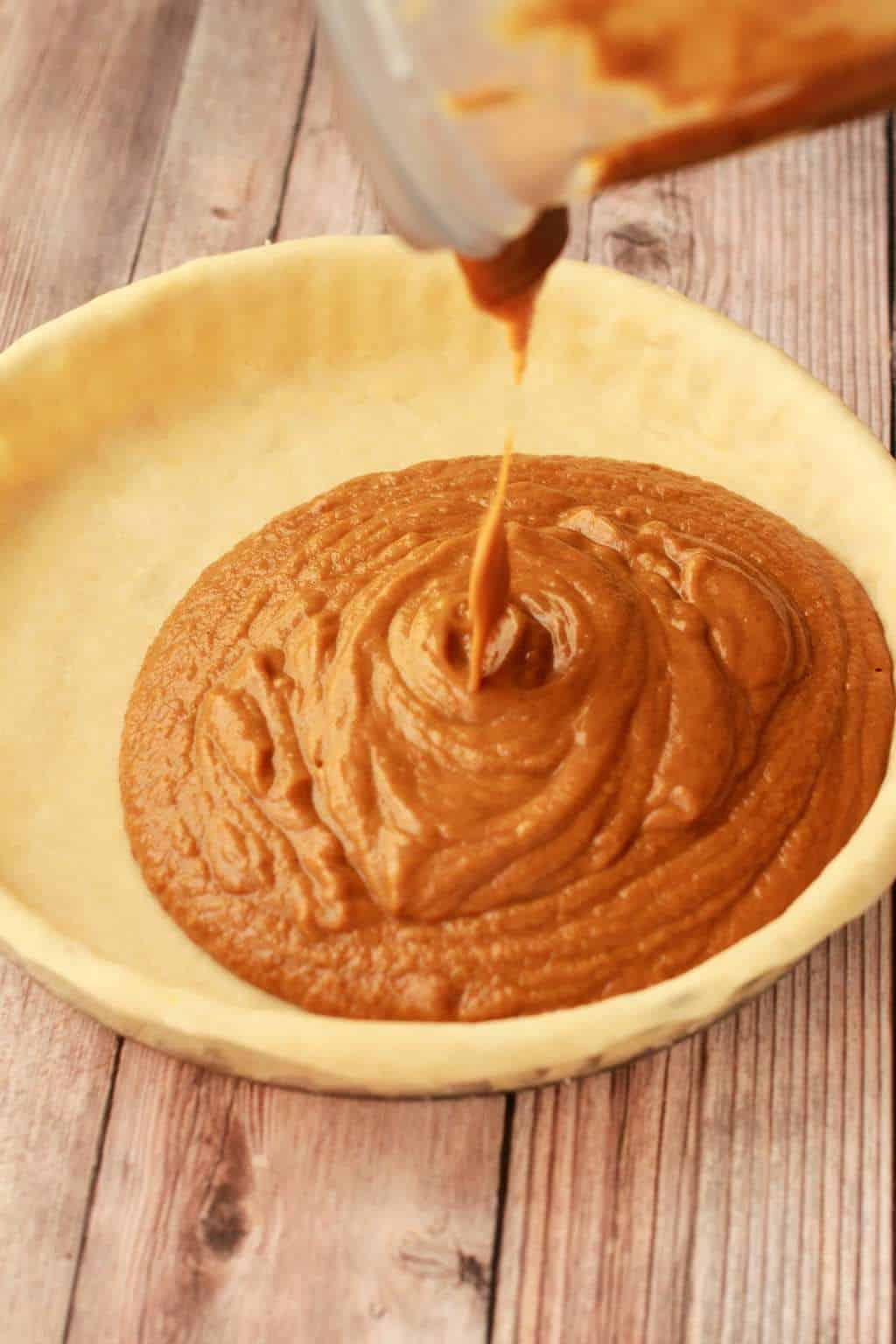 Pouring vegan pumpkin pie filling into a pie crust.