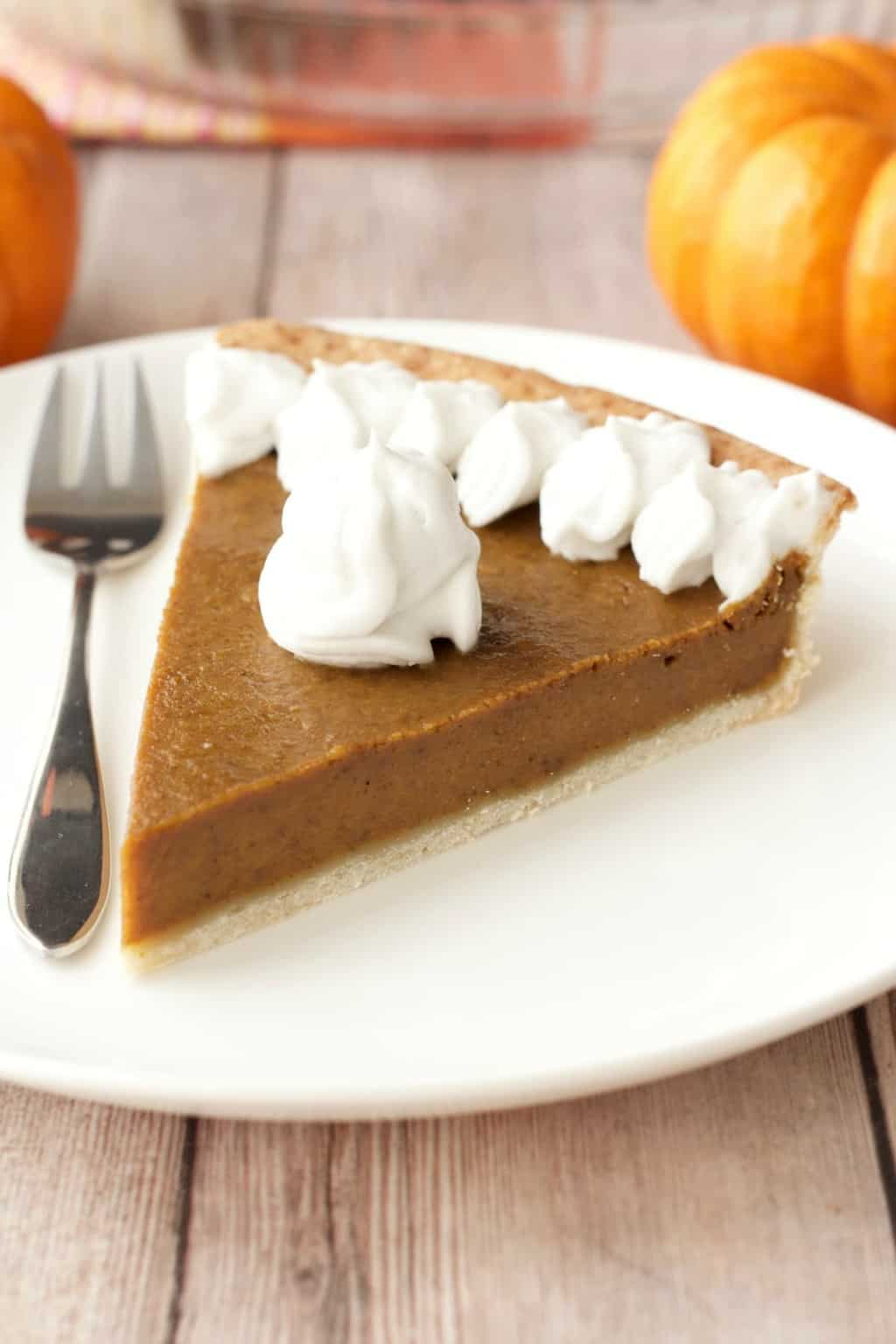 A slice of vegan pumpkin pie topped with whipped cream on a white plate with a cake fork.
