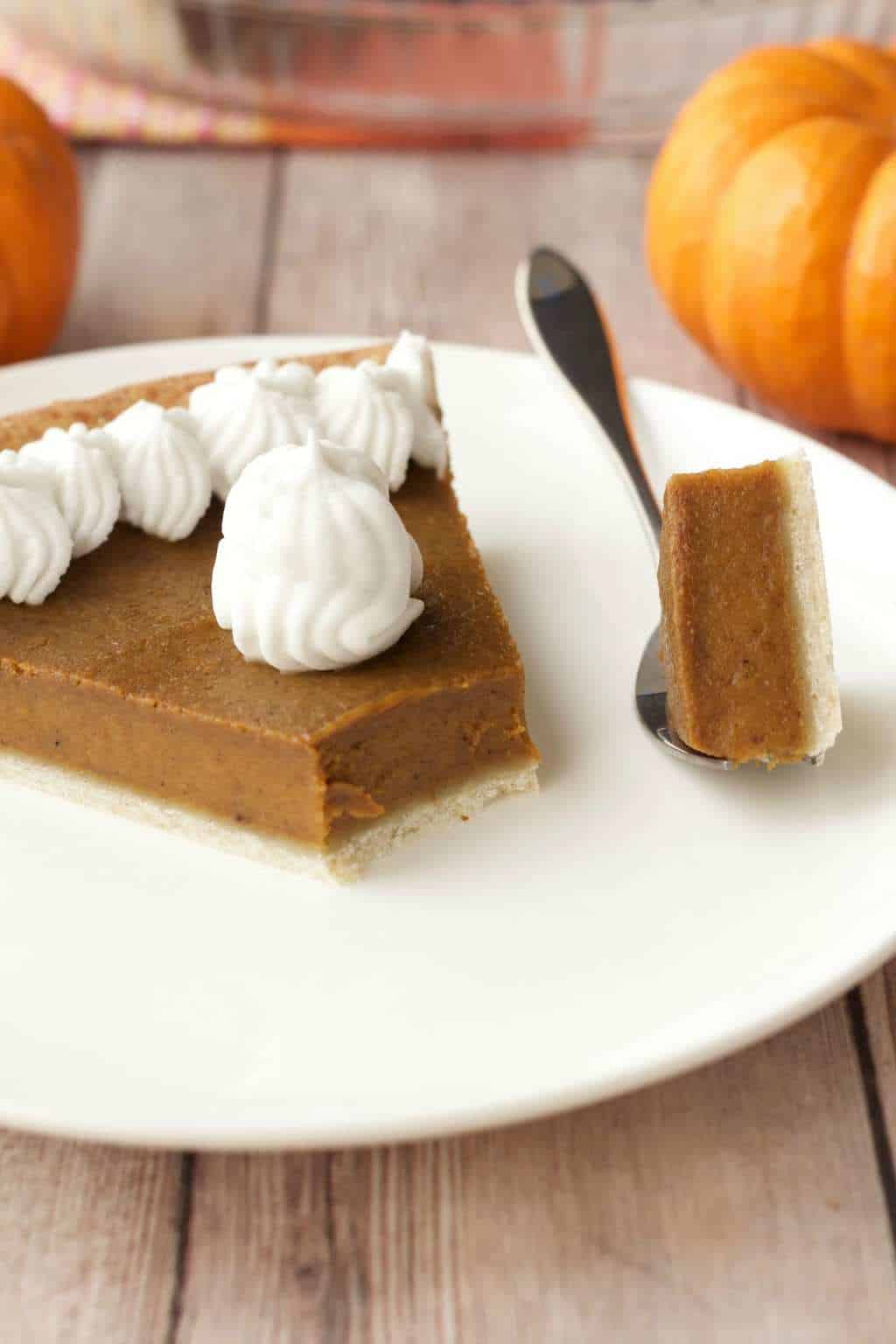 A slice of vegan pumpkin pie on a white plate with a cake fork.