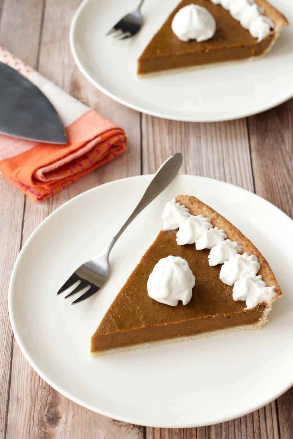 Slices of vegan pumpkin pie on white plates with cake forks.