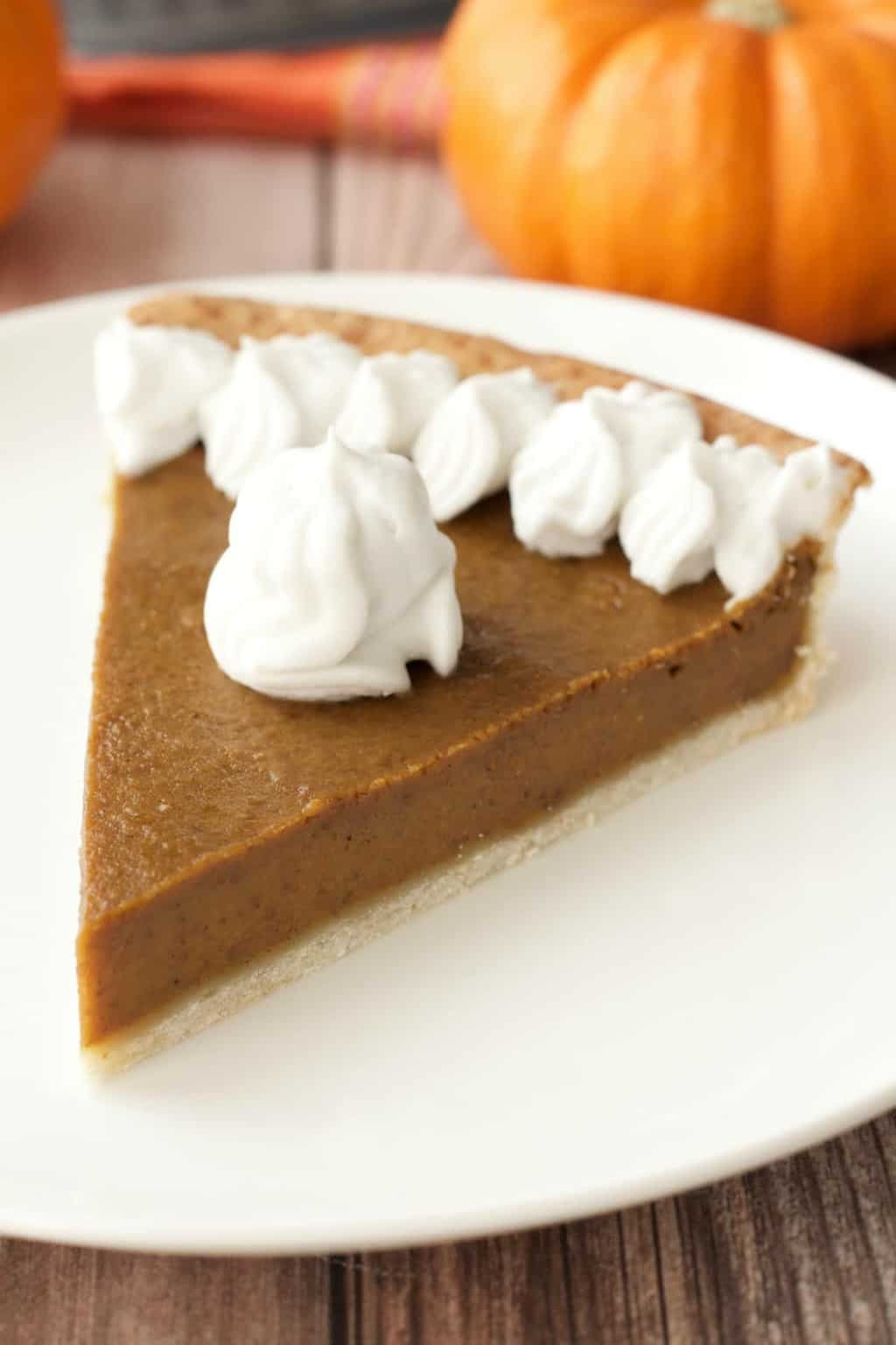 A slice of vegan pumpkin pie topped with whipped cream on a white plate.