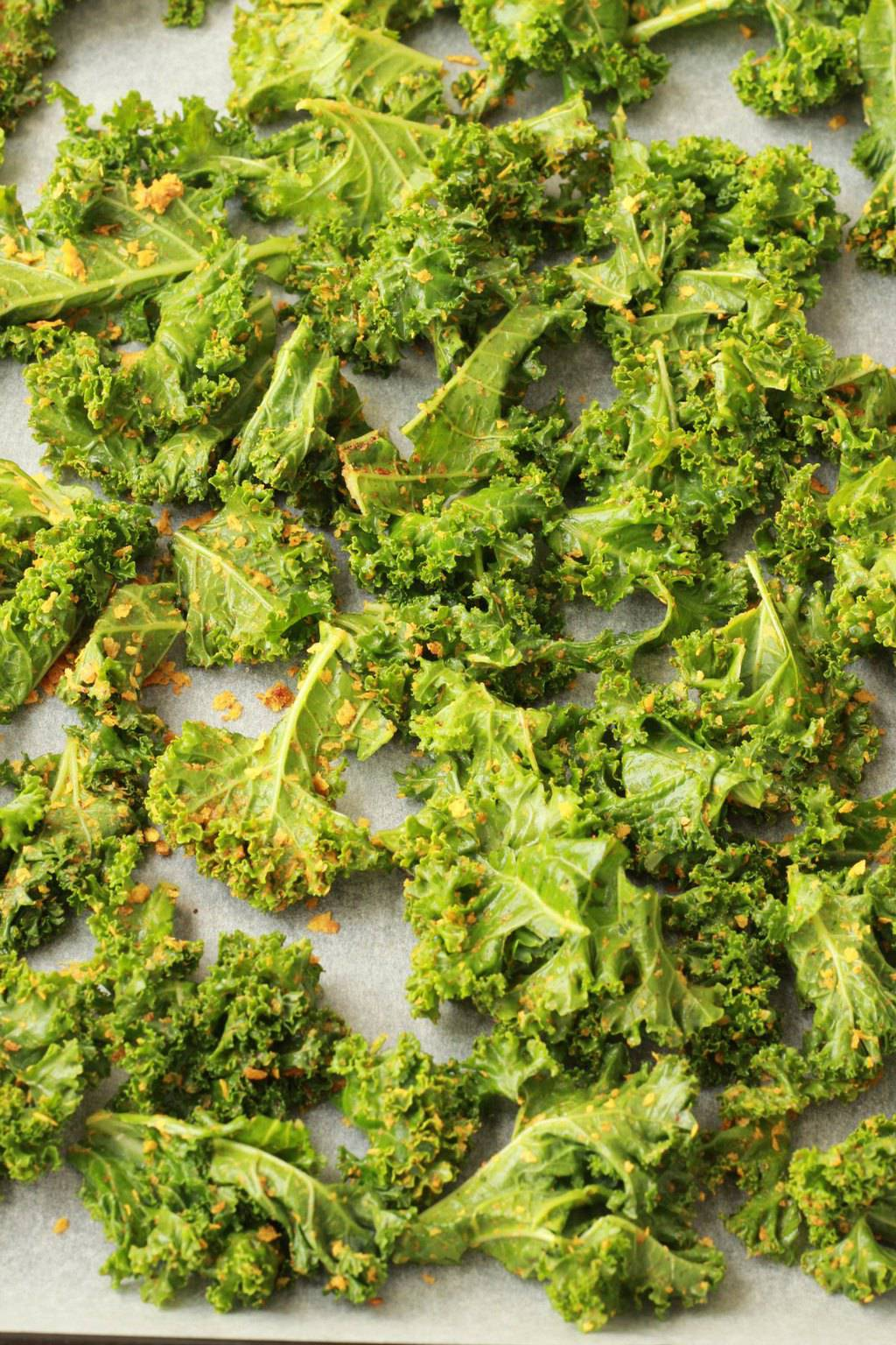 Making Easy Cheesy Kale Chips. Crispy, savory, cheesy and super healthy! #vegan #lovingitvegan #glutenfree #kalechips #snacks