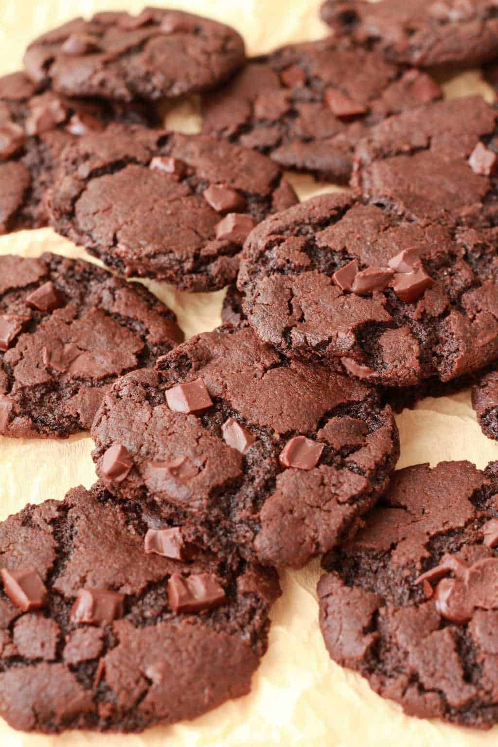Vegan chocolate cookies on yellow tissue paper.