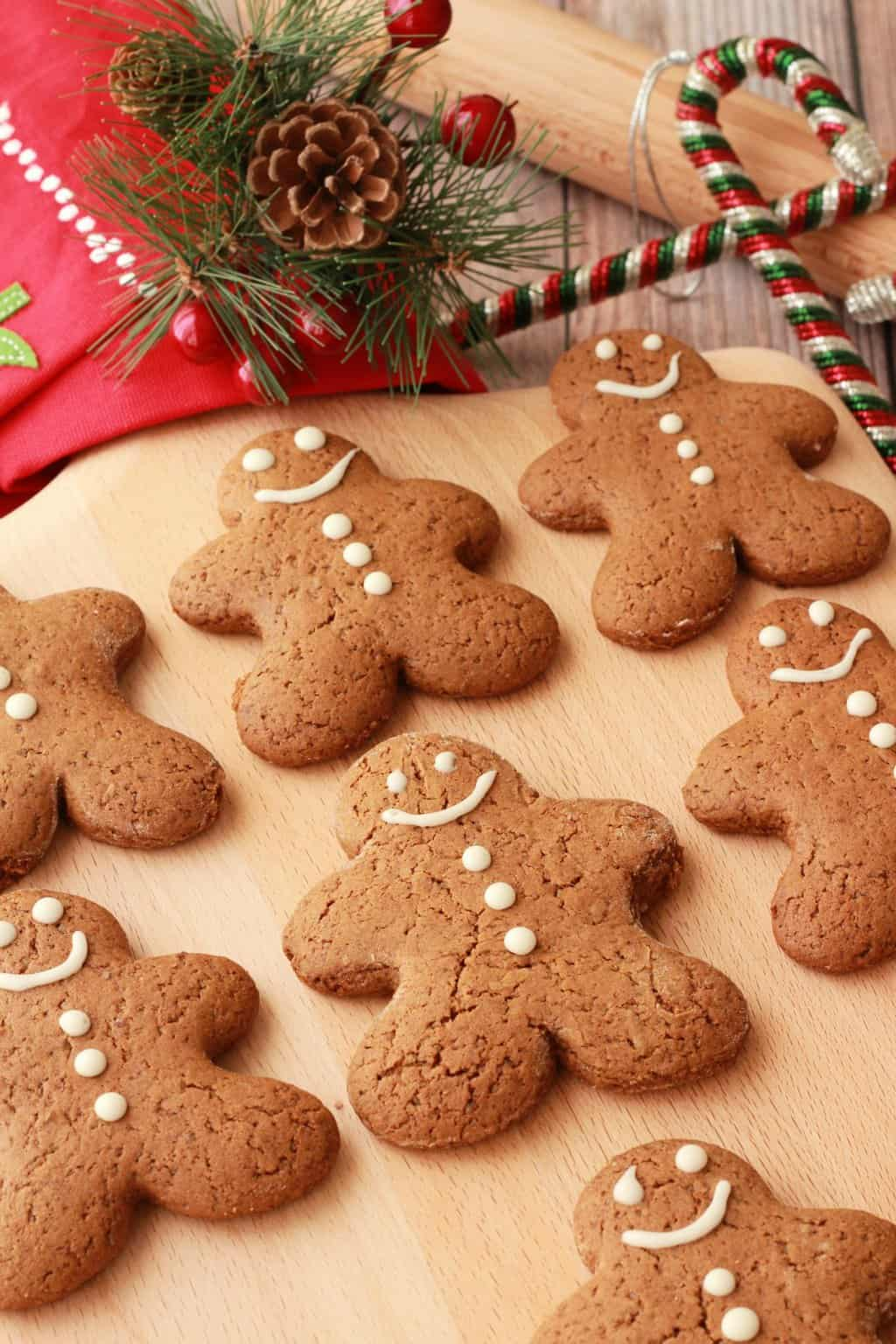Vegan gingerbread cookies on a wooden board with Christmas decorations in the background.