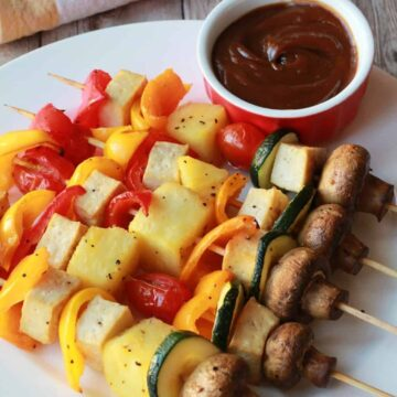 Vegetable skewers on a white plate.