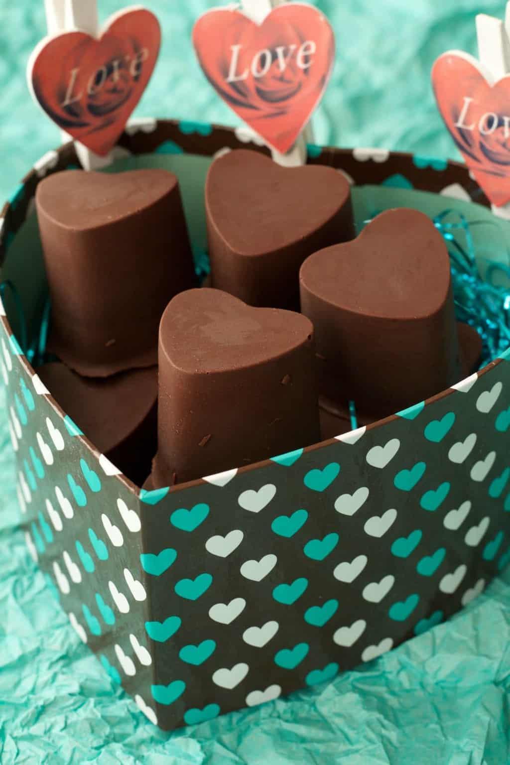 Heart-shaped vegan chocolate caramels in a heart shaped box.